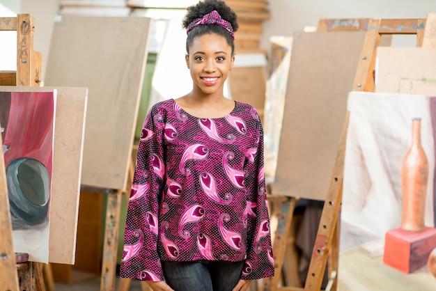Ritratto di un giovane studente africano in piedi nello studio di pittura