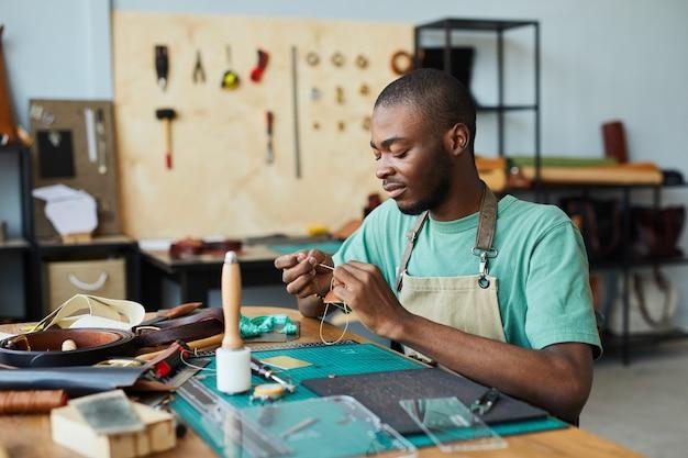 Ritratto di giovane artigiano afroamericano che lavora con la pelle nello spazio della copia dell'officina dei pellettieri