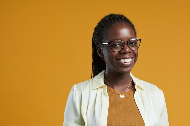 Ritratto di giovane donna afroamericana con gli occhiali e sorride alla macchina fotografica mentre posa contro...