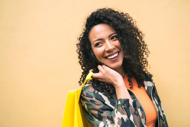 Ritratto di giovane donna latina afro-americana che tiene le borse della spesa su sfondo giallo. negozio e concetto di lifestyle.
