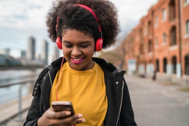 Ritratto di giovane donna latina afroamericana che utilizza telefono cellulare e che ascolta la musica con le cuffie nella via. all'aperto.