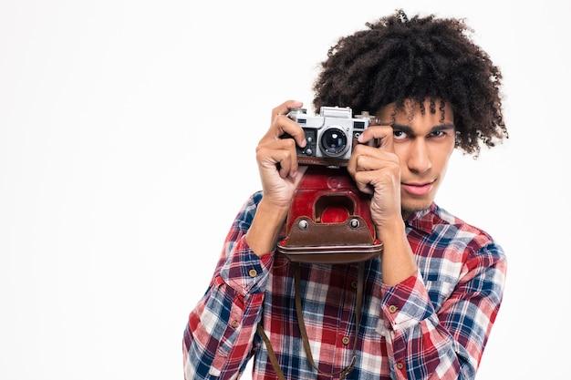 Ritratto di un giovane uomo afroamericano che fa foto su una fotocamera retrò isolata su un muro bianco