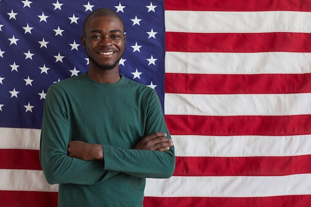 Ritratto di giovane uomo afro-americano in piedi con le braccia incrociate e sorridente contro la bandiera americana