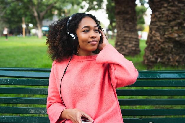 Ritratto di giovane donna afroamericana che ascolta la musica con le cuffie e il telefono cellulare nel parco.