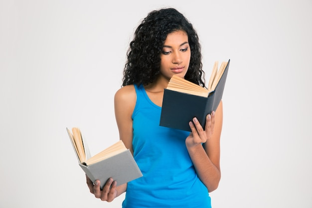Ritratto di un libro di lettura della giovane donna afroamericana isolato su un muro bianco