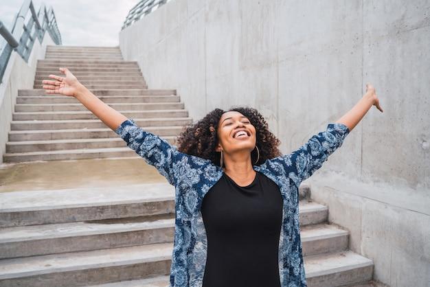 Ritratto di giovane donna afroamericana in piedi all'aperto con le braccia alzate e ridendo.