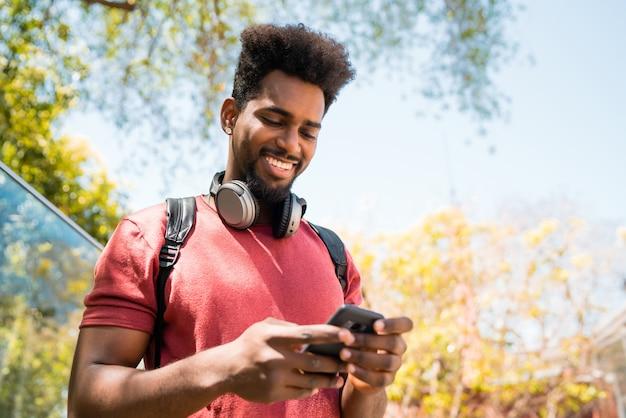 Ritratto di giovane uomo afro utilizzando il suo telefono cellulare all'aperto. concetto di tecnologia, urbano e stile di vita.