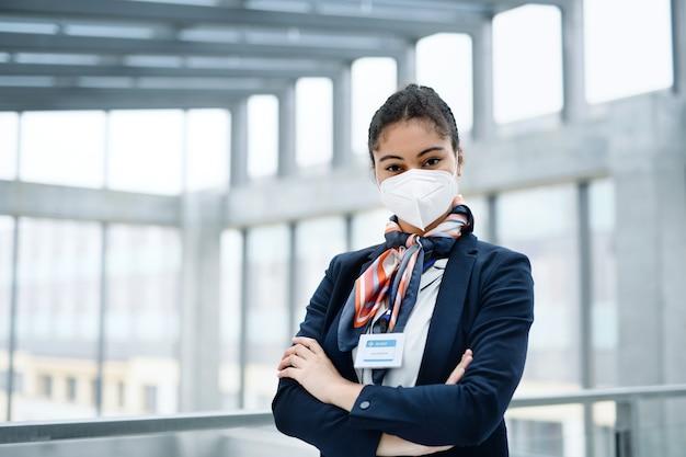Ritratto di giovane hostess che guarda la telecamera nella lounge dell'aeroporto coronavirus