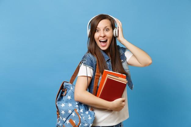 Ritratto di giovane studentessa eccitata stupita in vestiti di jeans con le cuffie dello zaino che ascoltano musica, tenendo i libri di scuola isolati su fondo blu. istruzione al college universitario di scuola superiore.