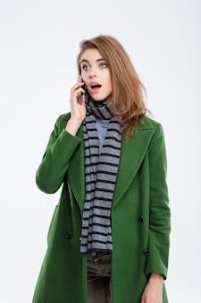 Ritratto di una giovane donna stupita che parla al telefono isolato su uno sfondo bianco