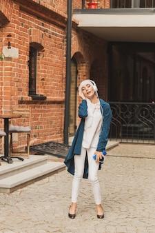 Ritratto di giovane donna musulmana araba che ascolta musica con cuffie e balli. femminismo, indipendenza della donna e concetto di svago.