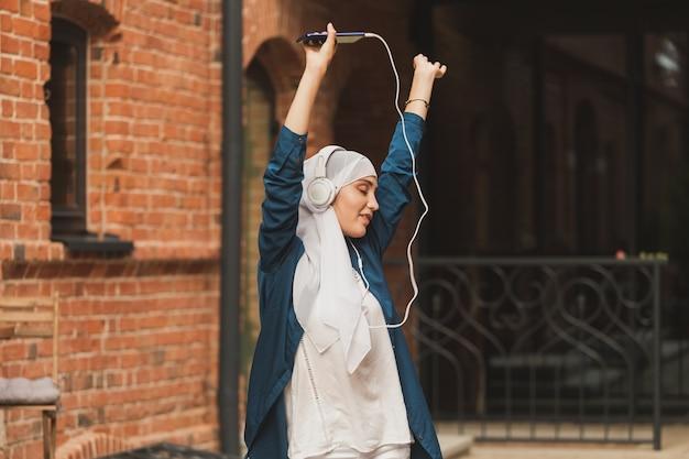 Ritratto di giovane donna musulmana araba che ascolta musica con le cuffie e balla il femminismo woman