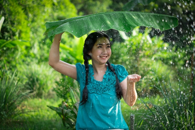 Ritratto di una giovane donna asiatica con i capelli neri che tiene una foglia di banana sotto la pioggia sullo sfondo del giardino verde