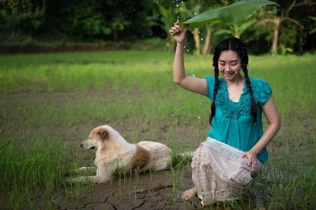 Ritratto di una giovane donna asiatica con i capelli neri che tiene una foglia di banana sotto la pioggia