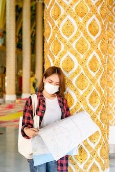 Ritratto di una giovane donna asiatica backpacker in piedi e tiene in mano una mappa cartacea nel bellissimo tempio thailandese, cerca direzione