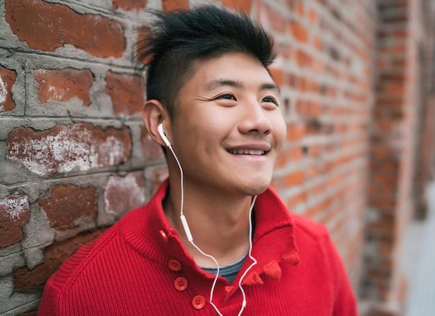 Ritratto di giovane ragazzo asiatico che ascolta la musica con gli auricolari all'aperto contro il muro di mattoni. concetto urbano.