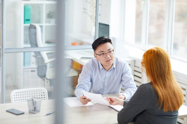 Ritratto di giovane uomo d'affari asiatico intervistando giovane donna per posizione di lavoro in un ufficio moderno, copia dello spazio