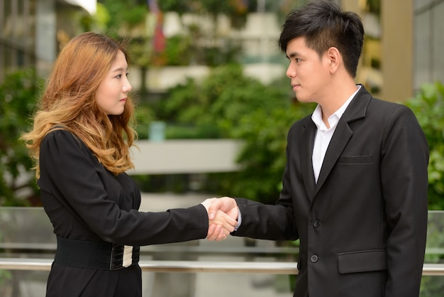 Ritratto di giovane uomo d'affari asiatico e giovane imprenditrice asiatica insieme al parco della città all'aperto