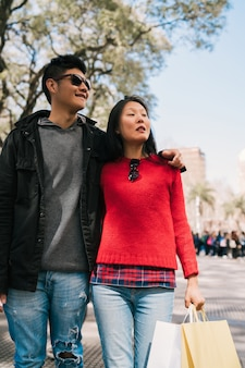 Ritratto di giovane coppia asiatica innamorata che cammina in città dopo lo shopping. concetto di negozio.