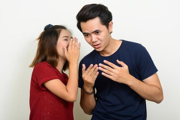 Ritratto di giovani coppie asiatiche che bisbigliano insieme