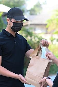 Ritratto di giovane fattorino asiatico in maschera protettiva che consegna cibo al cliente.