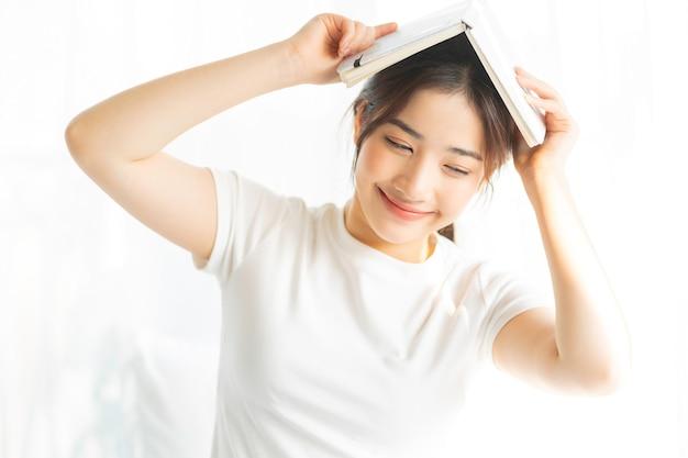 Ritratto di una giovane ragazza asiatica, leggendo un libro e bevendo caffè