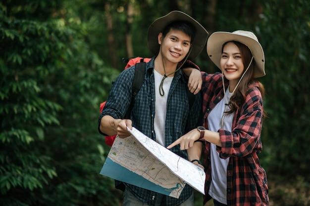 Ritratto giovane uomo asiatico bello con zaino e cappello da trekking e bella ragazza in piedi e controllando la direzione sulla mappa cartacea mentre si cammina sul sentiero nel bosco, concetto di viaggio zaino