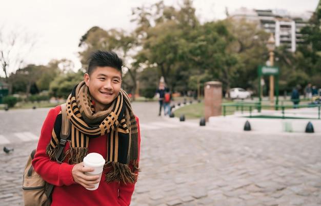 Ritratto di giovane uomo asiatico che beve una tazza di caffè mentre si cammina all'aperto in strada