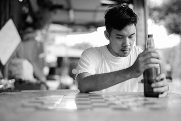 Ritratto di giovane uomo asiatico ubriacarsi nelle strade all'aperto