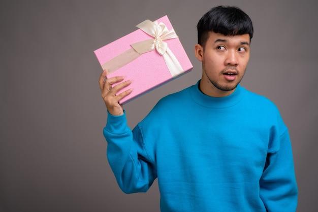 Ritratto di giovane uomo asiatico azienda confezione regalo