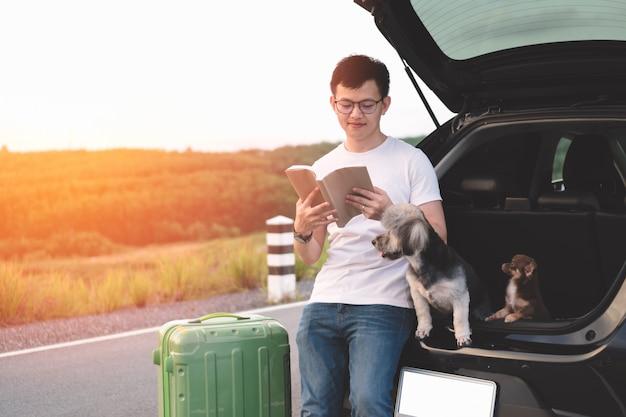 Ritratto del giovane libro di lettura asiatico dell'uomo mentre sedendosi nel tronco aperto dell'automobile con i suoi cani.