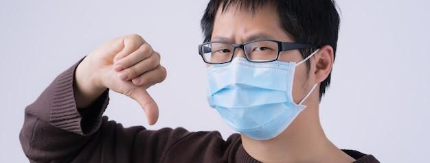 Ritratto di giovane uomo asiatico, che dice no all'infezione da coronavirus con l'uso di una maschera facciale chirurgica medica blu isolata su sfondo bianco, primo piano, primo piano.
