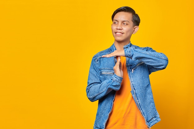 Ritratto di giovane uomo asiatico che mostra gesto di timeout su sfondo giallo