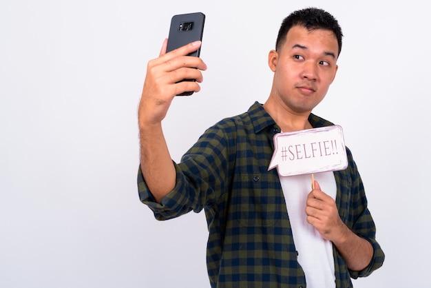 Ritratto di giovane uomo asiatico prendendo selfie con segno di carta