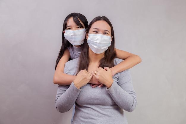 Ritratto di giovane madre asiatica con la figlia che indossa la maschera. madre e figlia che indossano una maschera per proteggere covid 19, quarantena. resta a casa il concetto.