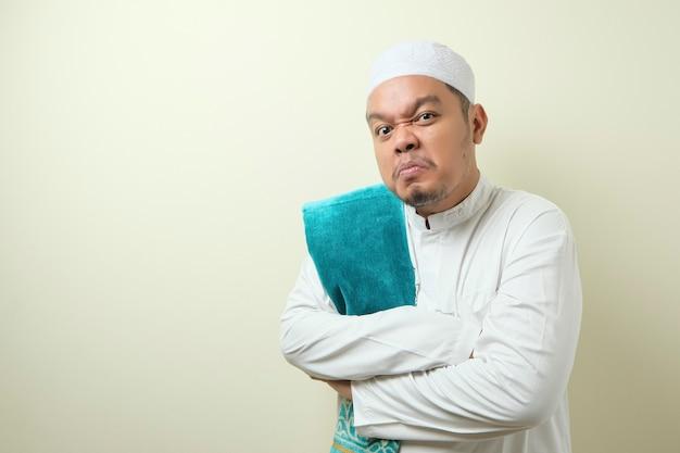 Ritratto di un giovane uomo musulmano asiatico che indica il suo orologio da polso, capo manager che avverte del concetto di tempo. il ragazzo sembra arrabbiato contro il muro d'avorio