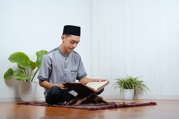 Ritratto di giovane uomo musulmano asiatico che legge il sacro corano su ramadan kareem a casa.