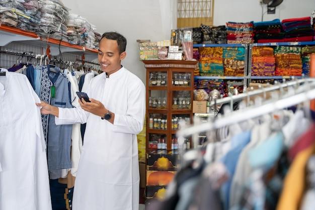 Ritratto di un giovane uomo musulmano asiatico shopping per i vestiti in negozio
