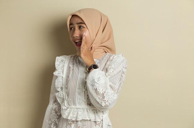 Ritratto di giovane donna musulmana asiatica che indossa l'hijab gridando e urlando