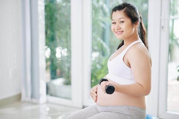 Ritratto di giovane donna incinta asiatica che tocca la sua pancia quando fa esercizio con manubri e sorridente