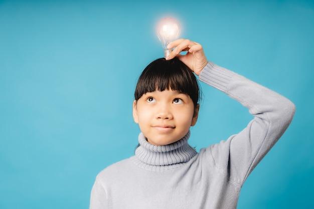 Ritratto di giovane studente asiatico e ragazza che tiene in mano una lampadina che brilla sulla sua testa e pensa, idea e innovazione educativa del concetto di bambino