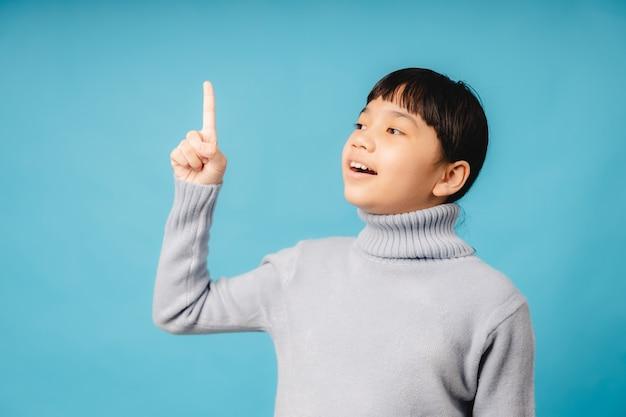 Ritratto di giovane studente asiatico e ragazza che punta verso l'alto e pensa, idea e innovazione educativa del concetto di bambino