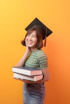 Un ritratto di giovane studente asiatico che indossa il cappello di laurea su sfondo di studio.