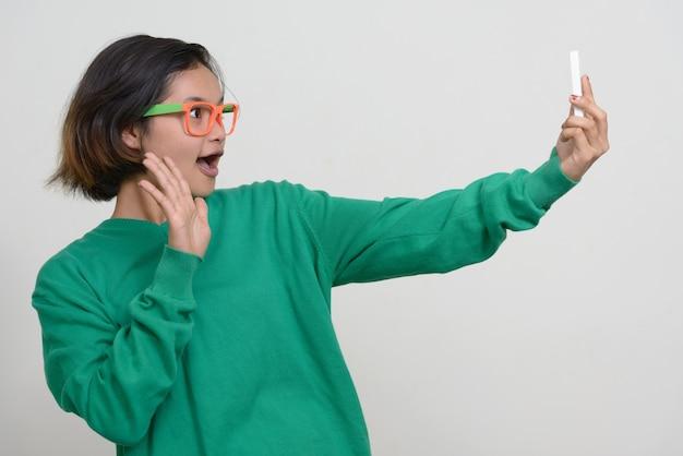 Ritratto di giovane adolescente asiatica con i capelli corti contro il muro bianco