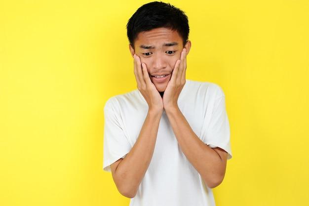 Ritratto di giovane adolescente asiatico infelice uomo spaventato, isolato su sfondo giallo
