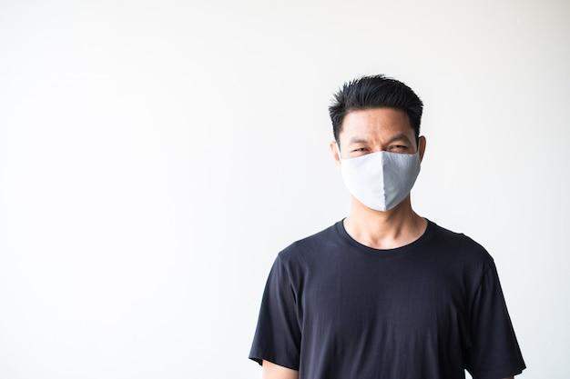 Ritratto di giovane asiatico che indossa la maschera di tessuto fatto in casa