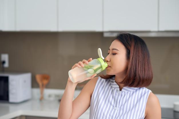 Ritratto di giovane donna asiatica che beve bevanda detox in cucina. concetto sano, concetto di cibo per la perdita di peso.
