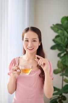 Ritratto di giovane donna asiatica che mangia pillola di vitamina per l'assistenza sanitaria a casa.