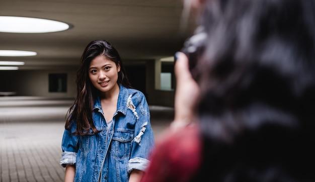 Ritratto di una giovane donna asiatica in posa mentre qualcuno le scatta una foto
