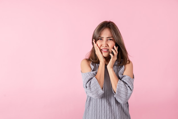 Ritratto di una giovane donna asiatica sconvolta dalle cattive notizie ascoltate da uno smartphone